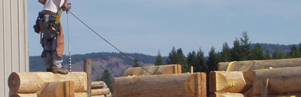 Picture of a man standing on a partially build log home wall, drilling through the logs for electrical.