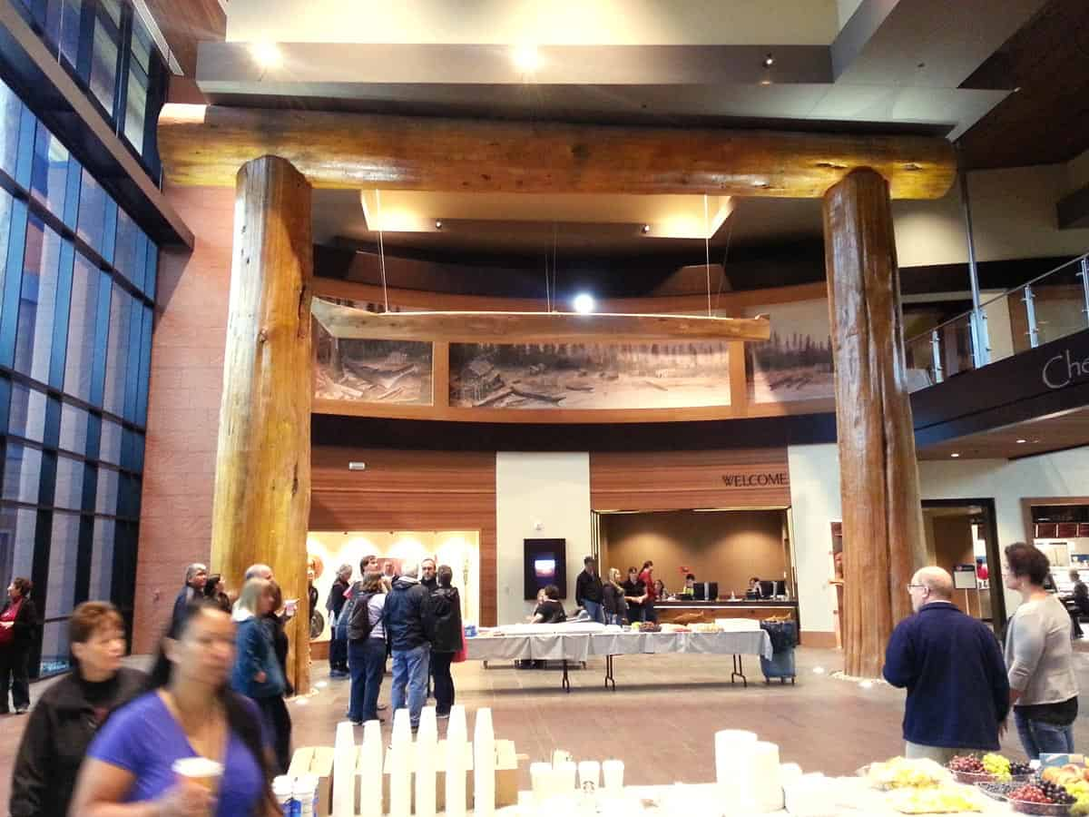 Large two story building with huge custom wood beams and people walking about.