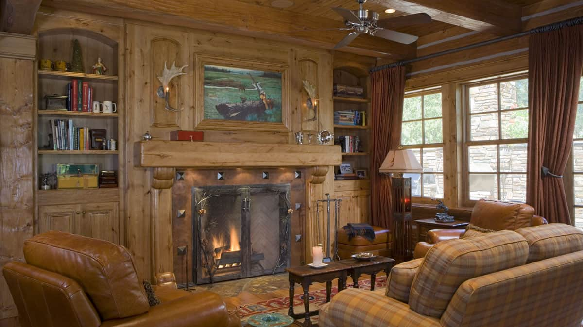Sitting room with a wood framed fireplace and book cases.