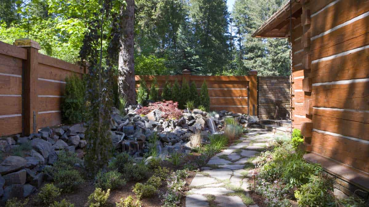 Garden outside a log home, landscaped with rocks and shrubs.