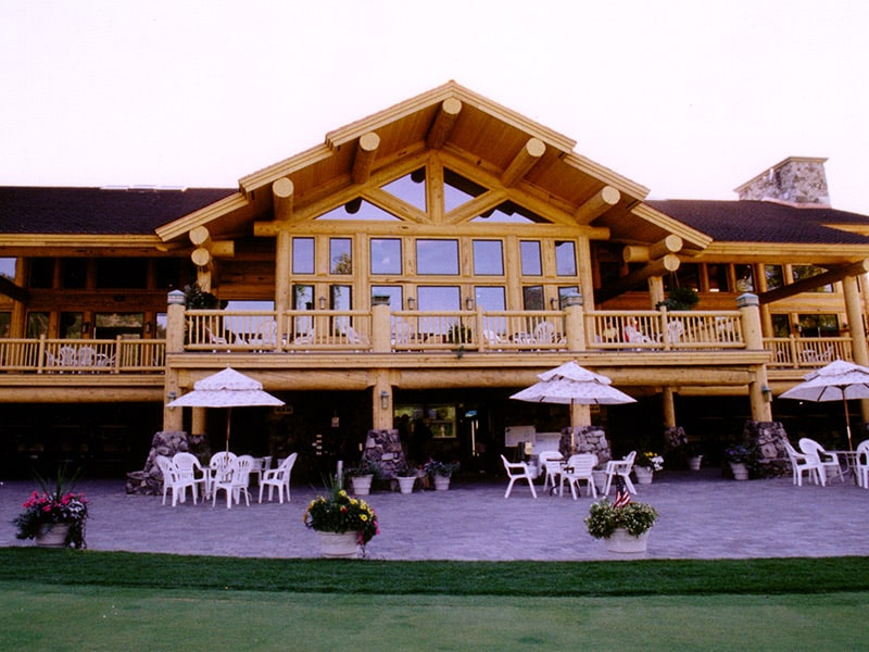 View of Hidden Lakes Golf clubhouse deck and outdoor dinning area. Exterior is all log construction.