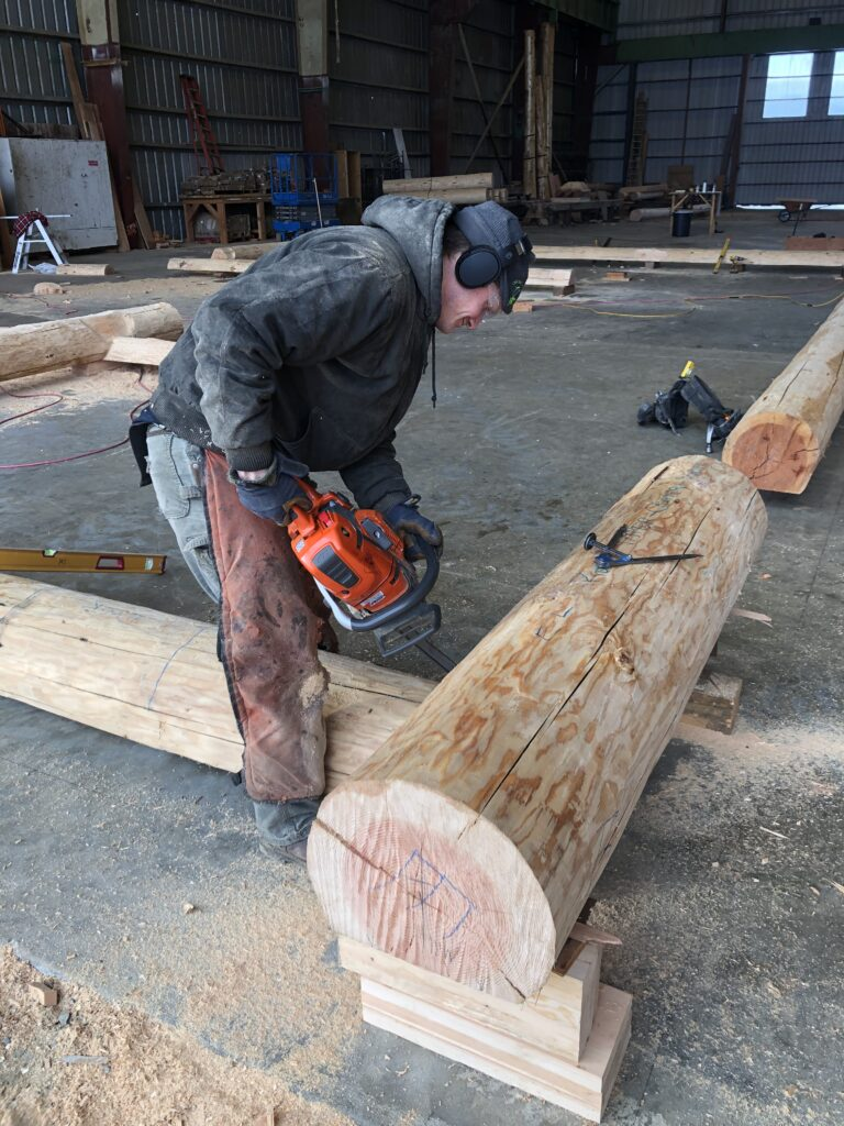 Image of a log crafter using a chainsaw on a log